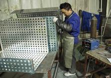 正在对冲孔铝单板进行焊接的王师傅
